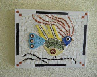 Colorful wall hanging of handmade ceramic bird with background of mozaic.