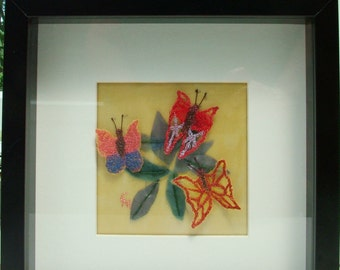 Butterfly textile art picture in black box frame.