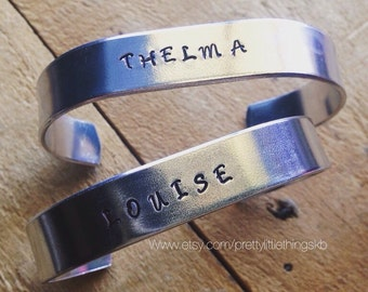 Hand Stamped Aluminum Cuffs with Thelma and Louise. Two cuffs included. Adjustable sizing.