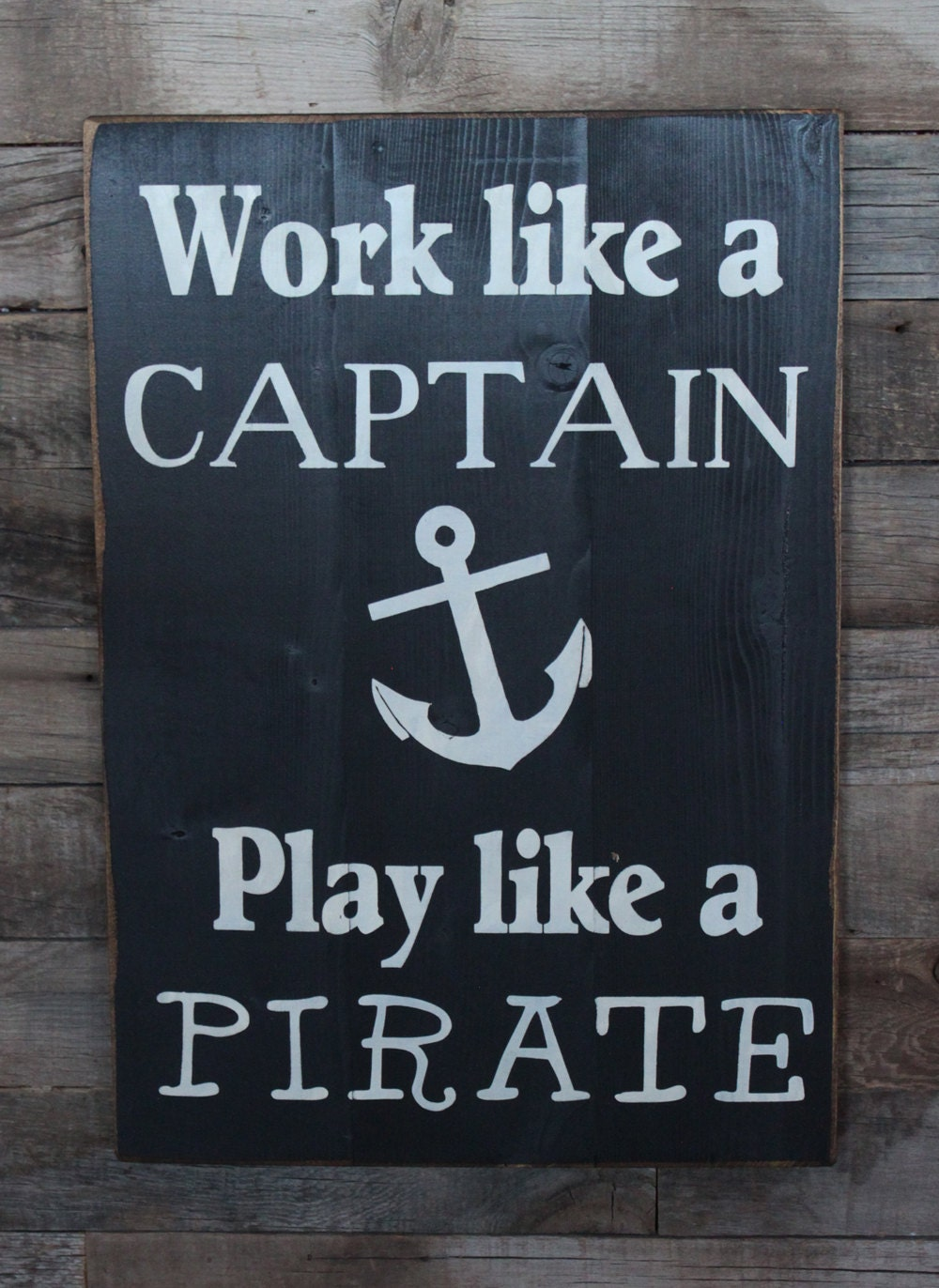 large wood sign work like a captain play like a pirate