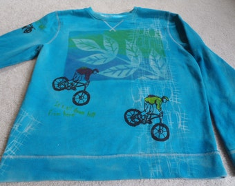 Two mountains bikers on a man's XL sweatshirt, discharged, dyed, and silk screened in turquoise, green,yellow, red violet & brilliant blue