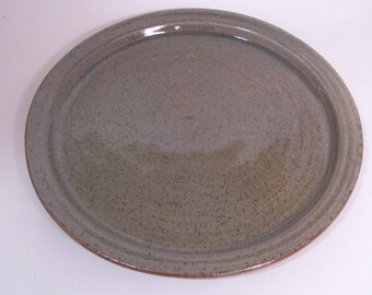 Hand thrown dinner plate with raised side. Glazed in celadon green.. 26 cm.