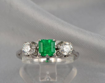 Distinctive natural emerald and diamond three stone engagement ring