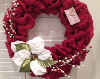 Red burlap bubble wreath with white poinsettia and berries for Christmas