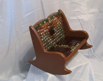 Decorative mini rocking chair with glass stones and tiles on front section.