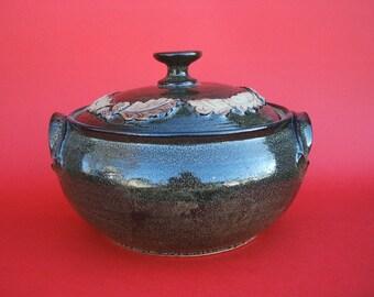 Hand thrown stoneware casserole with raised oakleaf decoration.21cm x 16cm.