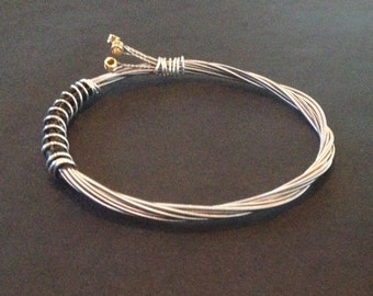 A handmade recycled guitar string bracelet/bangle bound with silver coloured wire.