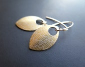gold feather earring in anodized aluminum. sterling silver and gold earrings.