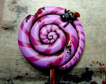 Dirty, bloody and bitten lollipop with a small visitor: a black fly! Fuchsia and maroon. Brooch, pendant or fridge magnet (choose)