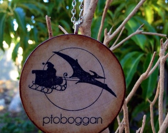 Pterodactyl pulling a Ptoboggan Christmas Ornament on Hand-Stained Wood