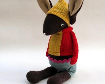 Brown Woollen Rabbit - Handmade plush sculpture wearing red woollen pullover and felt shorts.