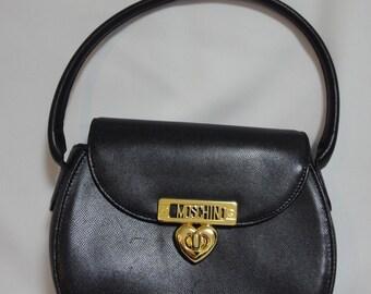 Vintage MOSCHINO black leather handbag, oval shape purse with a golden logo closure with heart shape charm.