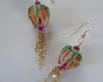 Sunset Rosebud Earrings are glowing Art glass rosebuds trailing sparkling stamens of gold, pouring from faceted ruby beads.