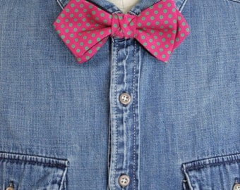 Bow tie tied with pink and green polka dots.
