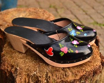 Mid-heel black leather clogs, in solid black or handpainted with the 'northern pattern'.