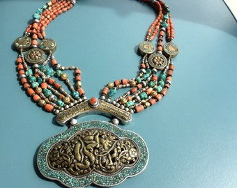 Tibettan vintage necklace, impressive silver en brass pendant. striking medallions, turquoise inlay, turquoise and coral beads. Boho jewelry