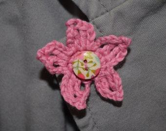 Handmade pink crochet flower with a button centre