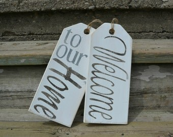 """Front door decoration.  Wood welcome sign.  Distressed, rustic """"Welcome to our Home"""" tag set in white."""