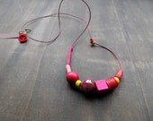 Red leather with a mix of beads and crochet details for this long summerfun necklace in shades of fuschia lemon red and pink