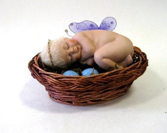"Baby 4"" angel in a birdsnest with basket and eggs handcrafted in porcelain from a vintage mold"