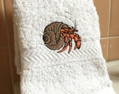 Bright orange hermit crab in natural brown shell, embroidered on white hand towel