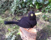 Knitted blackbird with poseable wire feet
