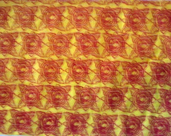 Sheet of yellow tissue paper handprinted with abstract flower design in red