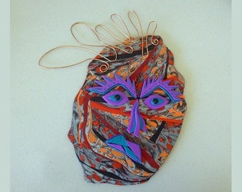 Troubled Tracy Grumpy Gremlin Mask Polymer Clay Wall Art in Red, Orange, Black, Purple, and Blue