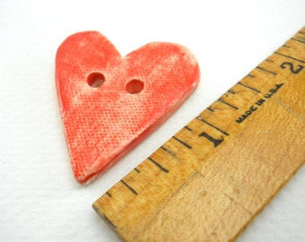 bright red heart-shaped button, hand made ceramics, textured, stone-washed denim finish, perfect accent for a hat, purse or sweater