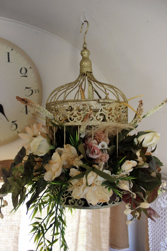 gold and blush floral arrangement in birdcage