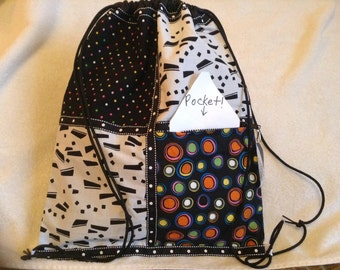 black and white geometrics with added color black ripstop nylon drawstring backpack with outside zipper pocket