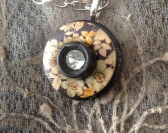 Antique floral buttons with black background on a silver chain