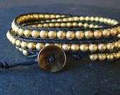 Wrap bracelet with 22k gold plated stardust beads on a black waxed cotton cord