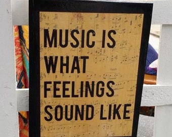Music is What Feelings Sound Like woodblock with sheet of music in background
