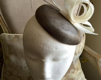 Gorgeous grey round base fascinator with white sinamay loops and feathers. Simple and sophisticated!
