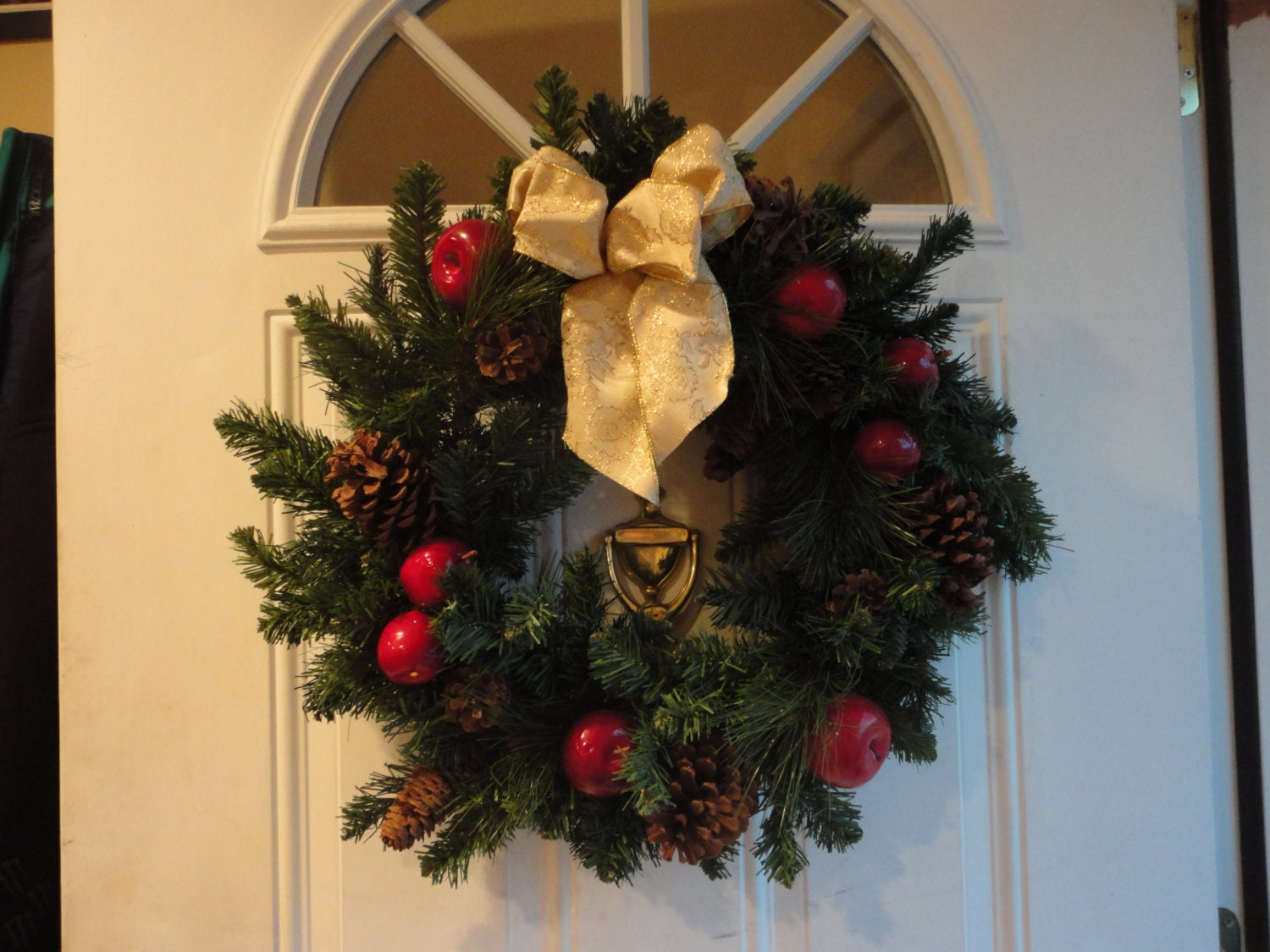 Large, bushy wreath with apples, pine cones and a large gold bow