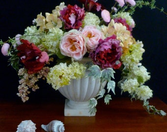 Large, lush floral arrangement in magentas, pinks, and pale green.