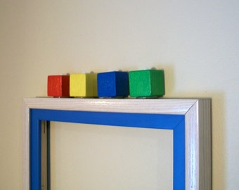 Colorful mirror with wooden blocks on bright blue and white frame
