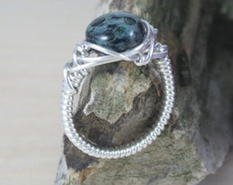 Green and black glass bead wrapped in sterling silver ring