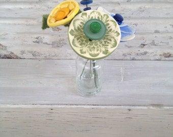 light green, blue, and yellow button flower bottle bouquet