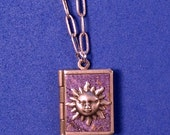 Sun Love Book, purple and silver, holding 14 ways to say 'I love you' from around the world.