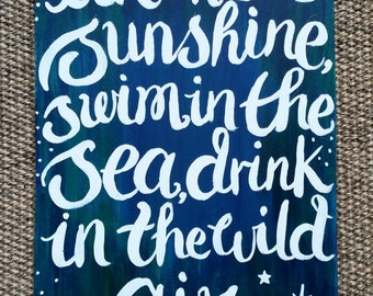Live in the Sunshine, Swim in the Sea, Drink in the Wild Air wooden hanging sign.