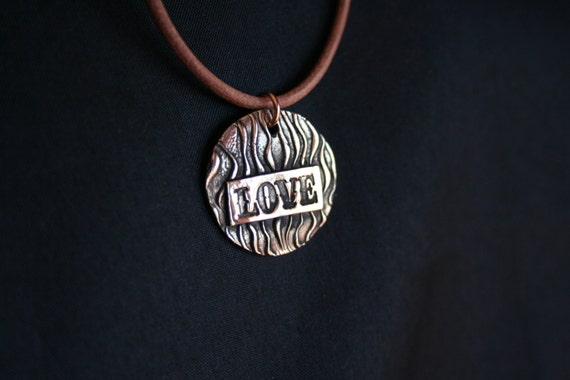 """Love on a wavey backgound in Bronze.  25mm or 1"""".  Comes with a brown leather necklace with bronze endcaps and clasp"""