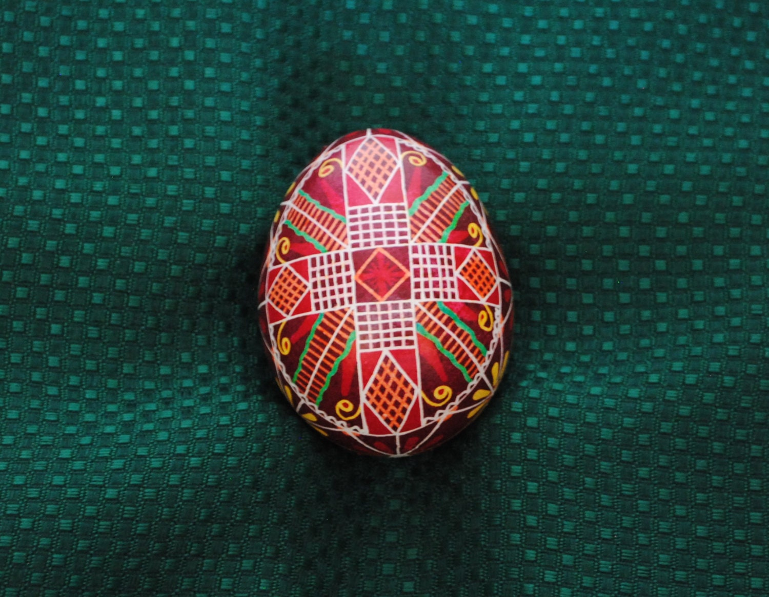 pysanky on chicken egg dark red and scarlet prominent colors