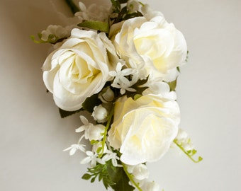 Ivory silk wedding jacket corsage. Made from artificial roses, bouvardia, lily of the valley, and rose leaves.
