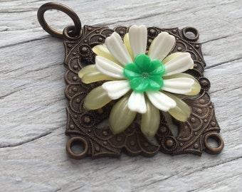 Antiqued brass pendant with green white and pale yellow flowers 45mm