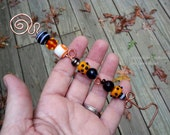 hammered copper candle snuffer beaded with orange black and white glass beads