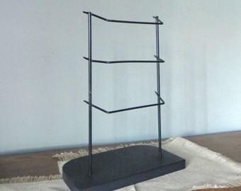 Vintage black metal display rack with three rods on wooden base