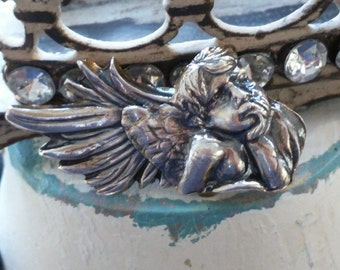 dreaming winged cherub as a silver pin