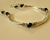 Handmade leather and silver tube bracelet. Facetec beads, contemporary, classic, understated, adjustable.